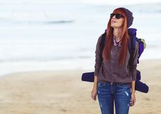 Millennial backpacker in sunglasses against blurry beach. Digital composite of Millennial backpacker in sunglasses against blurry beach Royalty Free Stock Photos