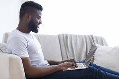 Millennial black man working on laptop in home office. Home office. Positive african american man working on laptop, typing on keyboard, free space stock photos