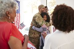 Millennial African American  soldier embracing his family after returning home,close up, selective focus. Millennial black soldier embracing his family after stock image