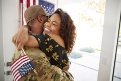 Millennial African American  soldier embracing his wife after arriving back home,close up stock photography