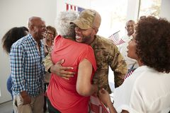 Millennial African American  soldier returning home to family embracing his grandmother,close up. Millennial black soldier returning home to family embracing his royalty free stock image