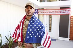 Millennial African American  soldier with US flag draped over his shoulders, looking to camera, close up. Millennial black soldier with US flag draped over his stock photo