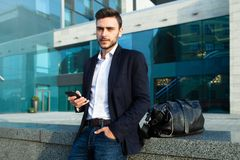 Millennial businessman with a mobile phone in his hands. Young successful business stylish man with a black leather bag. Walks on a city street against the stock image