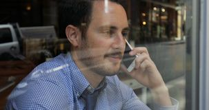 Phonecalls And Coffee Before Work. Millennial businessman is talking on the phone while enjoying a coffee in a cafe on his way to work stock video
