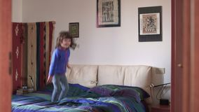 Millennial candid child playing and jumping on bed SF. An happy Millennial candid child is playing and jumping on bed at home stock footage