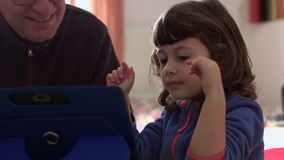 Millennial candid child playing on tablet close shot SF. Close shot of a Millennial candid child playing on a tablet and joking with dad stock video footage