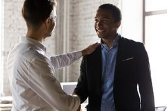 Caucasian boss handshake black employee greeting with success. Millennial Caucasian boss handshake tap shoulder of African American employee greeting with work stock photos
