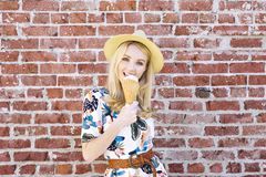 Millennial Caucasian Girl Licks an Ice Cream on a Hot Summer Day While Smiling. Hip young female with a fedora hat licks an ice cream on a hot day royalty free stock photo