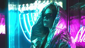 Millennial cool modern pretty girl smoking cigarette near glowing neon wall at night. Mysterious hipster. Beautiful. Stylish teen wearing shiny laser jacket and stock footage