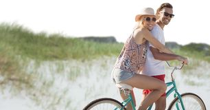 Millennial couple on bicycle against sand dune royalty free stock photos