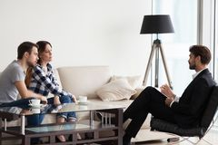 Millennial couple counselling at psychologist during therapy ses. Millennial husband and wife consulting with male psychologist or counselor talking about family royalty free stock images