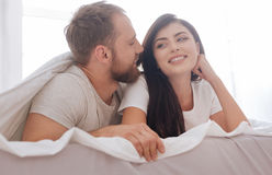 Millennial couple flirting in bed Stock Images