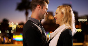 Millennial couple looking into each other`s eyes outdoors at night Stock Images