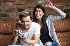 Millennial couple playing video games, young gamer with excited royalty free stock images