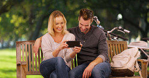 Millennial couple watching videos on smartphone together in the park Royalty Free Stock Images