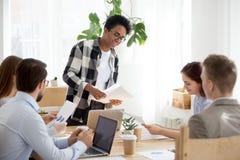 Millennial czarne żeńskie części papierkowej roboty zapomogi przy biurowym meeti zdjęcia royalty free