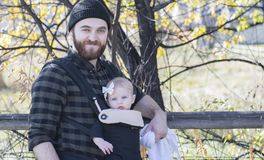 Millennial Dad with Baby in Carrier Outside Walking. On a Beautiful Fall Day stock images