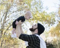 Millennial Dad Holding Baby Daughter Up Showing Affection Stock Images