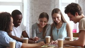 Millennial different ethnicity friends sitting at table assembling jigsaw puzzle