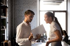 Diverse employees argue over financial report in office. Millennial diverse employees standing holding financial paperwork, disputing over statistics or contract stock photos