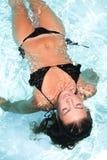 Millennial dziewczyna pławik przy basenem podczas lata zdjęcia royalty free