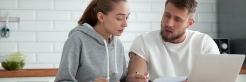 Millennial echtpaarzitting bij lijstlezing die leningsdocumenten controleren stock foto's