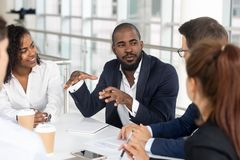 Black millennial boss leading corporate team during briefing in boardroom. Millennial employees gathered in boardroom for training, black boss ceo leader leading royalty free stock image