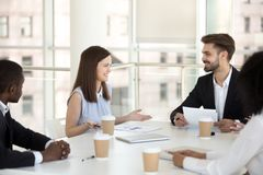 Millennial employees smiling negotiating at office briefing stock photos