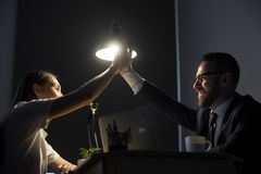 Two happy colleagues giving high five in office at night. Millennial employers making high five at night shift in business office. Two happy successful young Stock Photo