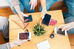 Millennial friends using their mobile smart phones in bar - Young people connecting on new trends social networks - Influencer royalty free stock photo