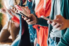 Millennial generation modern devices technology. Millennial generation. Colorful cropped closeup of young people holding smartphones. Modern devices royalty free stock photos