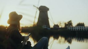 Millennial girl sits with phone on lake pier. Setting sun. Woman using shopping app outdoors. Old Dutch windmill. 4K. stock video