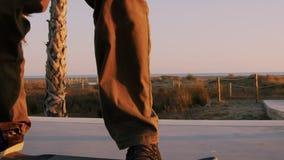 Millennial hipster skateboarder ritten in zonsondergang stock video