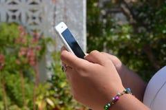 Millennial kvinna med mobiltelefonen i händer, utomhus royaltyfri bild