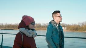 Millennial ludzie w okularach przeciwsłonecznych: młodego człowieka i kobiety przyjaciele chodzą przy quay zbiory wideo