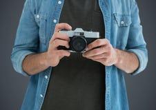 Millennial mężczyzna w połowie sekcja z kamerą przeciw popielatemu tłu obrazy stock