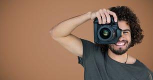 Millennial mężczyzna z kamerą przeciw brown tłu obrazy stock
