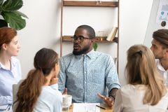 Millennial male businessman in glasses talking to colleague in office. Millennial black male businessman in glasses talking to listening colleague sitting at stock image