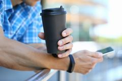 Millennial man hold smartphone with coffee cup stock photo