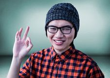 Millennial man making ok sign in green room Stock Photo