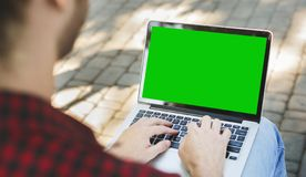 Millennial man typing on laptop with green screen. Millennial man typing on laptop with green chroma key screen, sitting outdoors, view over shoulder, panorama royalty free stock image
