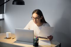 Millennial manager in glasses working on laptop and holding docu. Young casual businesswoman holding paper document and working on laptop in home office in Royalty Free Stock Photos