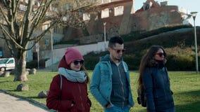 Millennial mensen in zonnebril: drie jonge volwassen vrienden lopen in stad stock videobeelden