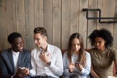 Millennial multiracial friends using mobile phones and talking a. Millennial multiracial friends using phones talking at meeting, diverse young people spending Royalty Free Stock Photos