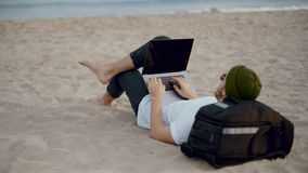 Millennial nomad works on laptop at beach stock footage