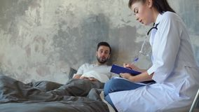 Millennial nurse making diagnosis while visiting patient stock video footage