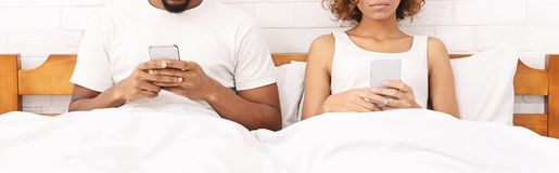 Millennial paar die in bed afzonderlijk met smartphones liggen stock foto