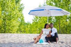 Millennial paarzitting door het strand onder paraplu terwijl het kussen royalty-vrije stock afbeeldingen
