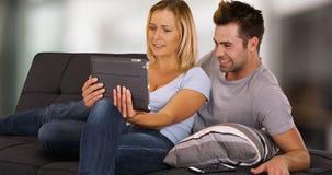Millennial par som tillsammans delar minnestavlan och håller ögonen på video på soffan royaltyfria bilder