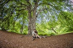 Millennial parsammanträde under ett stort träd royaltyfria bilder